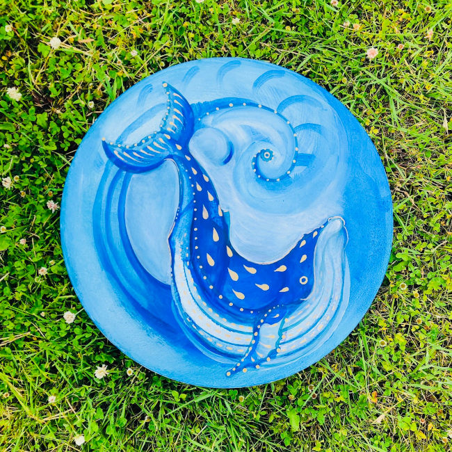 Circular blue painting of a blue whale in the sea